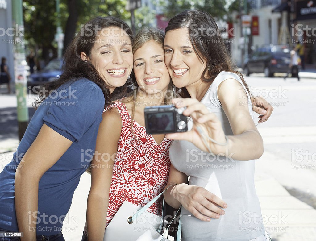 Three women outdoors taking self-portrait with digital camera smiling royalty-free stock photo