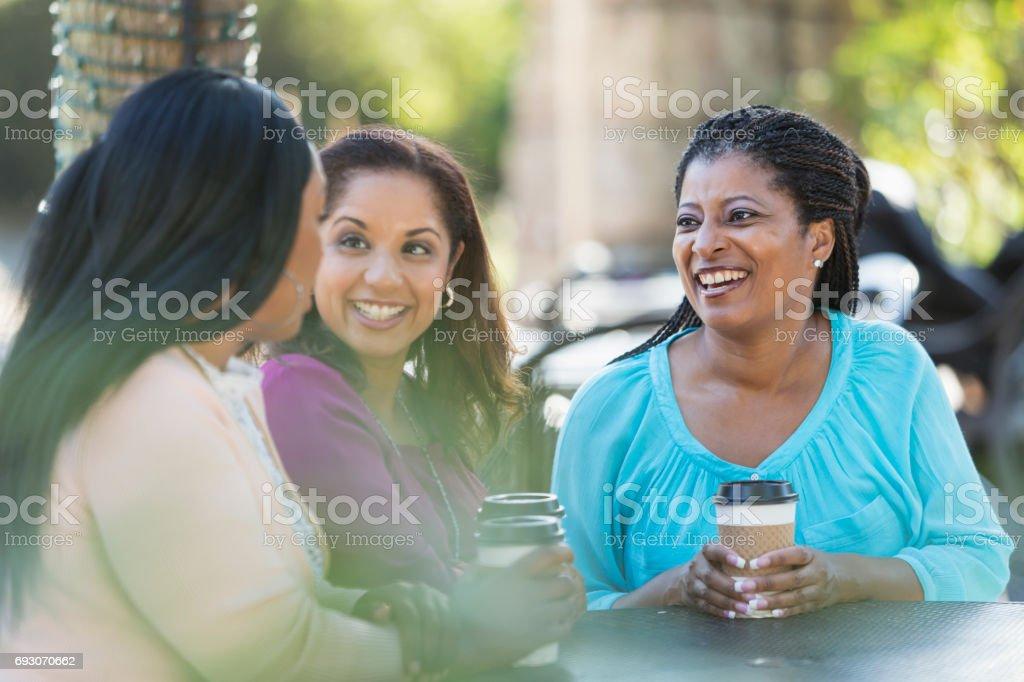 Three women outdoors talking, drinking coffee stock photo