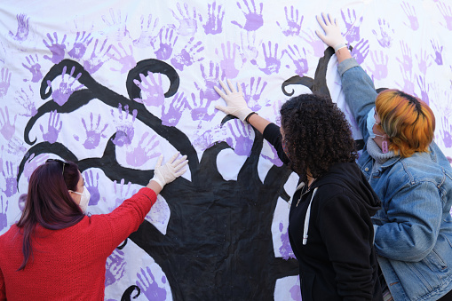 Three women participating in the International Day for the Elimination of Violence against Women participatory mural. 25 november.