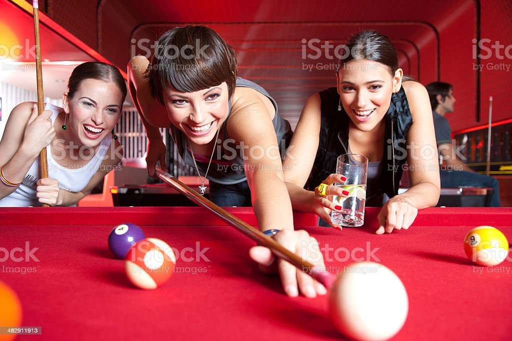 Three women playing pool and smiling stock photo