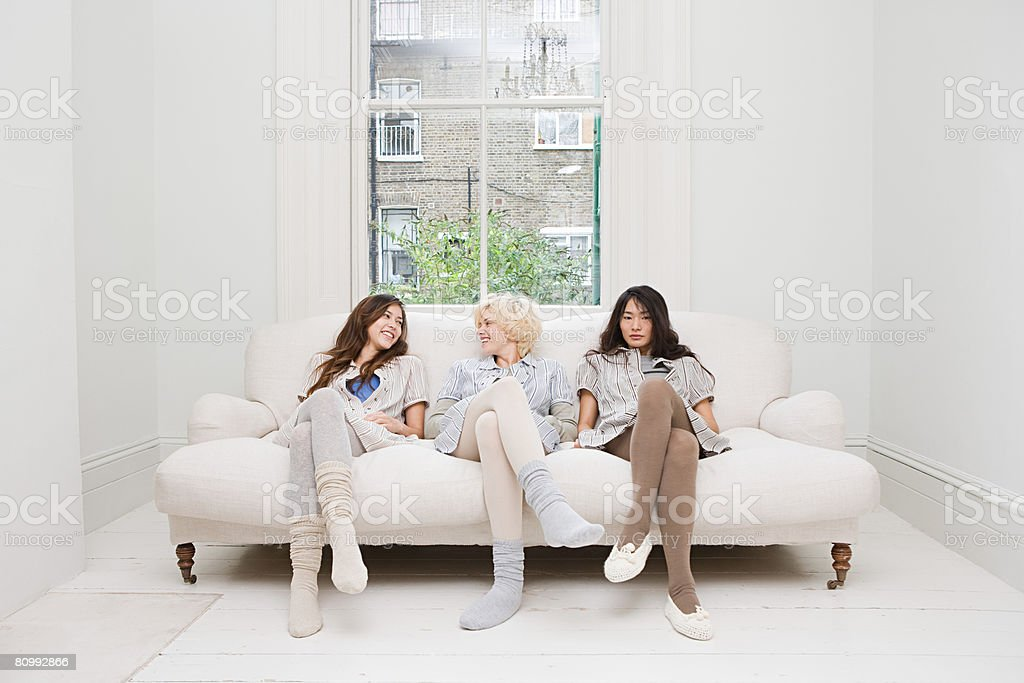 Three women sat on a sofa royalty-free stock photo