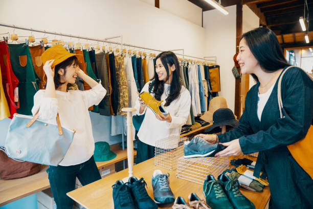 洋服店で一緒に買い物をする3人の女性 - 小売り ストックフォトと画像