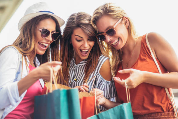 three women shopping together. - spending money stock pictures, royalty-free photos & images