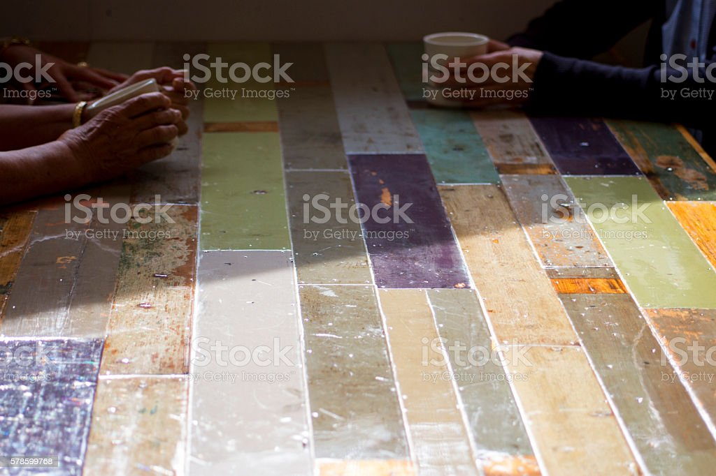 Three women sitting at a soft pastel colors' table There is a soft pastel colors' table. Three women are sitting around it. Two of them have coffee cups. Sun light shines a half of the table. Adult Stock Photo