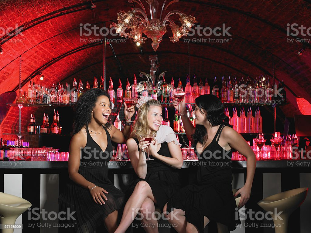Three women sitting at bar stock photo
