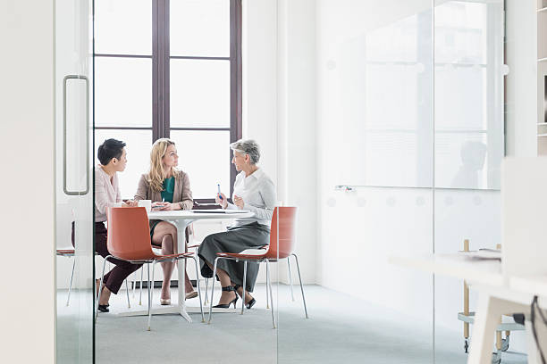 three women sitting at table in modern office - three people stock photos and pictures