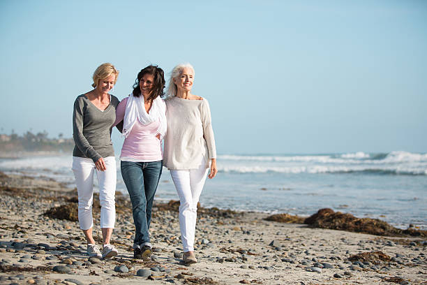 three women strolling on a beach. - 60 69 years stock photos and pictures