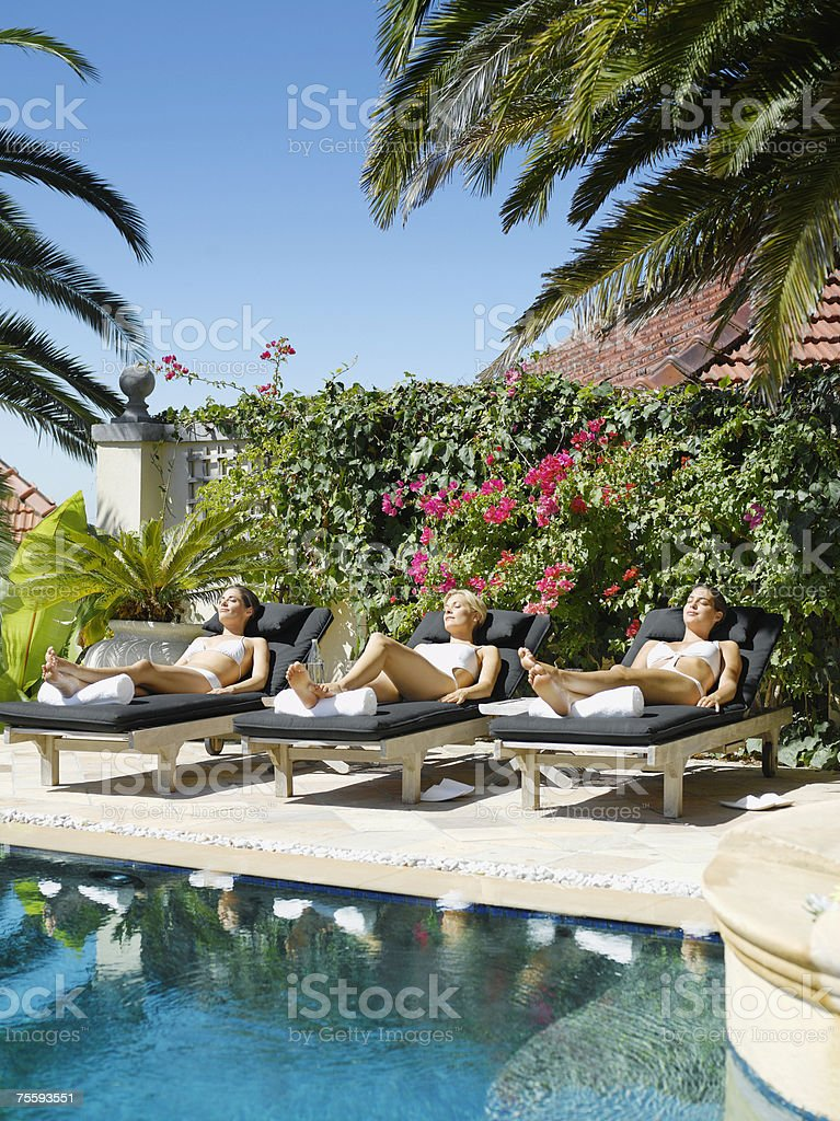 Three women sun tanning in lounge chairs by a pool royalty-free stock photo