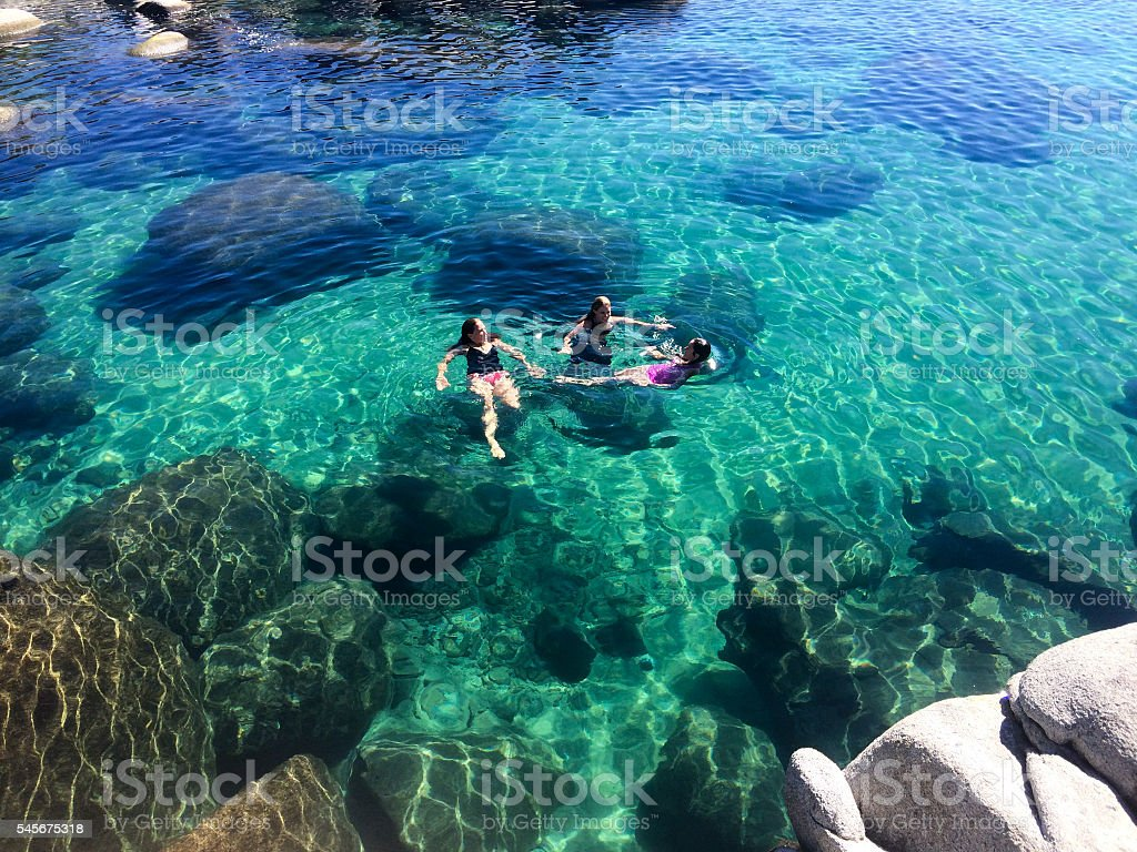 Three women swimming in Lake Tahoe, California stock photo
