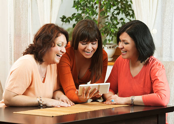 Three women using a digital tablet at home. stock photo