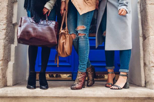 drei frauen tragen elegante schuhe und accessoires im freien. herbst modekonzept. damen halten frauen handtaschen - handtasche jeans stock-fotos und bilder