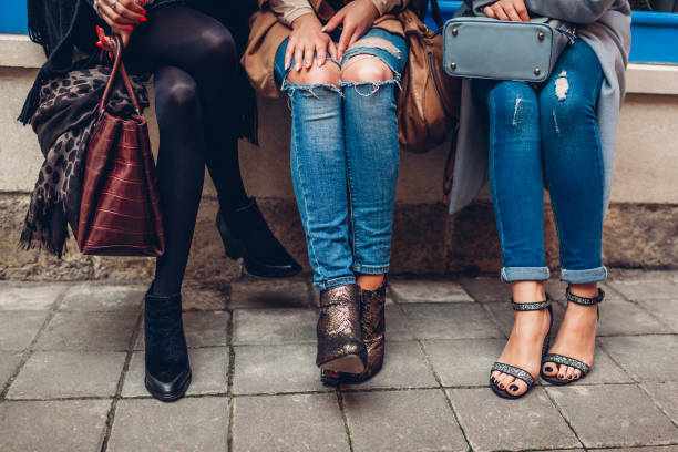 drei frauen tragen elegante schuhe und accessoires im freien. beauty-mode-konzept. - damen jeans sale stock-fotos und bilder