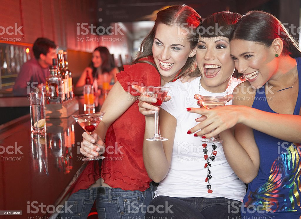 Three women with beverages in nightclub pointing and smiling royalty-free stock photo