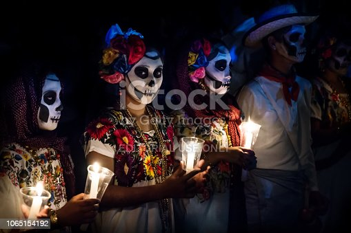 Merida, Cementerio General, Mexico - 31 October 2018: Three women with Catrina customes and man with white cowboy dress with skull make-up holding candels at the parade for dia de los muertos at the Festival Des Las Animas