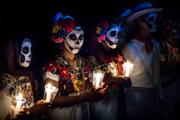 Three women with Catrina customes and man with white cowboy dress with skull make-up holding candels at the parade for dias de los muertos at the Festival Des Las Animas at the Cementerio General, Merida, Mexico stock photo