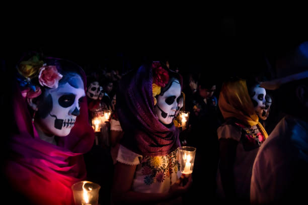 Three women with Catrina customes, scarves on their head and flowers in the hair with skull make-up holding candels surrounded by costumed people at the parade for dias de los muertos at the Festival Des Las Animas at the Cementerio General, Merida, Mexic stock photo