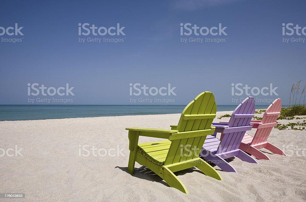 Three wooden chairs on beautiful deserted sandy beach stock photo