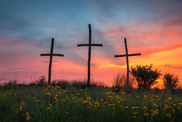 Three wooden crosses at sunset stock photo