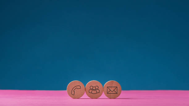 Three wooden cut circles with contact and communication icons Three wooden cut circles with contact and communication icons on them placed in a row on pink surface over blue background. With copy space. telephone directory stock pictures, royalty-free photos & images