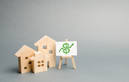 831745600 istock photo Three wooden houses figurines and a stand with green arrow up. Increasing the cost and liquidity of real estate. Attractive investing. rising prices or renting. The boom in the real estate market 1158581489