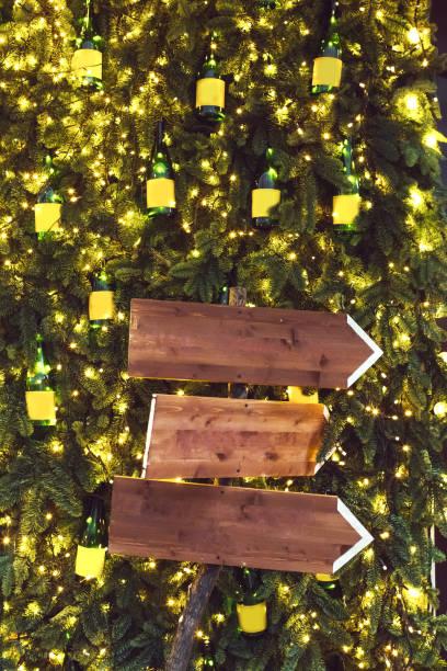 drei hölzerne zeiger auf hintergrund mit tannenzweigen in girlanden. lichter weihnachtsdekoration, silvester-party - heiratssprüche stock-fotos und bilder