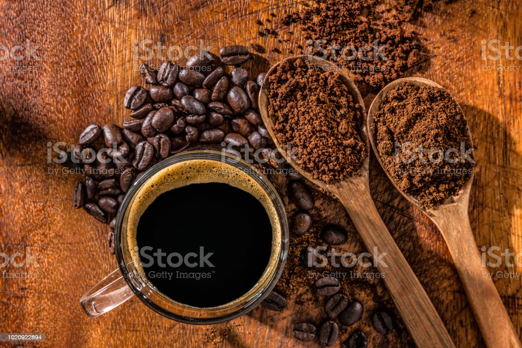 Three wooden spoons with coffee beans, instant coffee and grinded coffee in jute frame stock photo