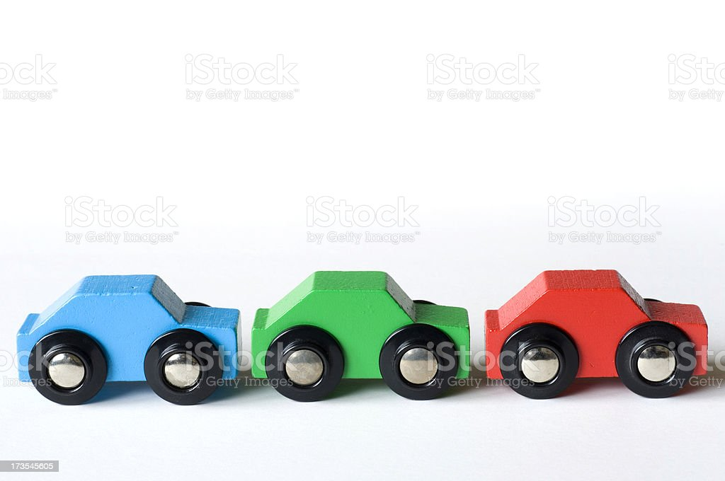 Three wooden toy cars in a row stock photo