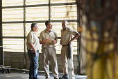 A group of three multi-ethnic workers, working for a trucking company, having a meeting. They are standing in a garage or warehouse by the rolling doors.