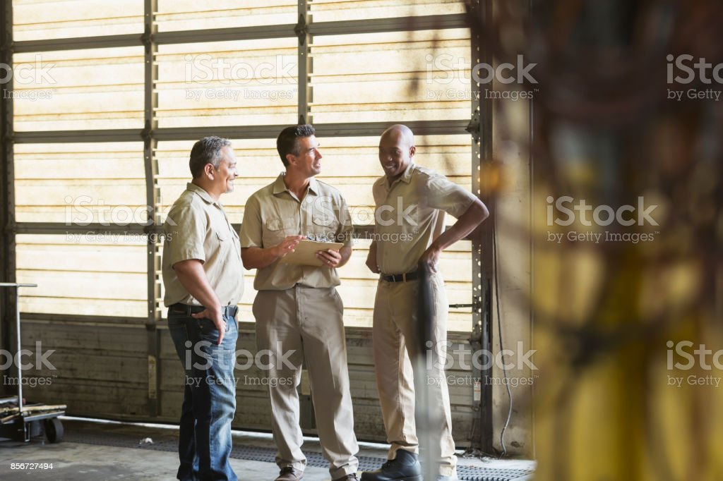 Three workers for trucking company having meeting stock photo