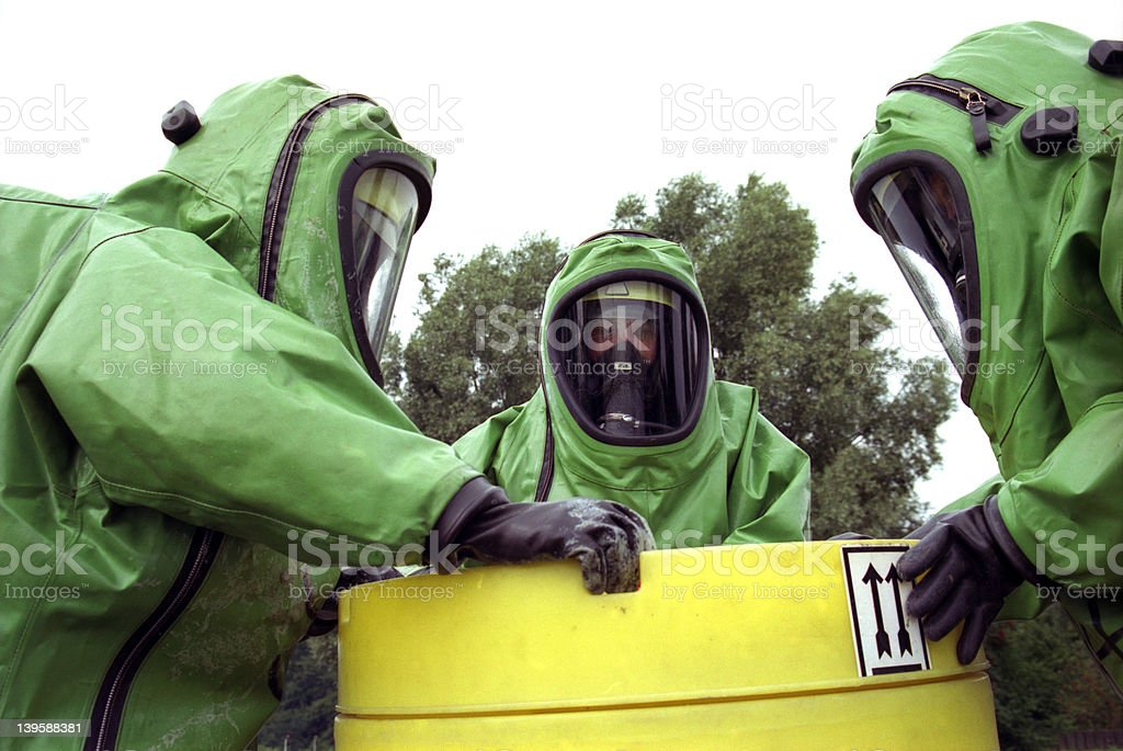 Three workers in green chemical protection suits stock photo