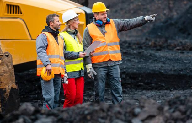 Drei Arbeiter im Steinbruch mit schweren Maschinen – Foto