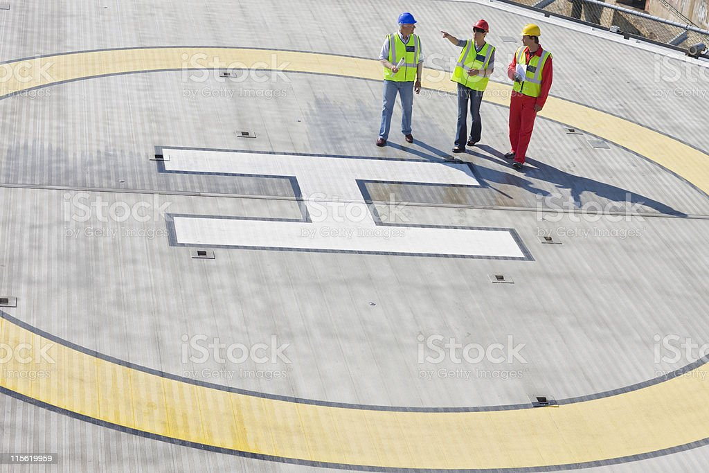 Three workers on helideck stock photo