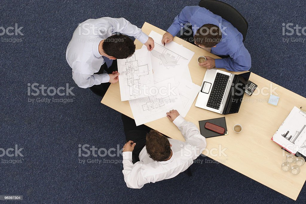 three working business people over plans royalty-free stock photo
