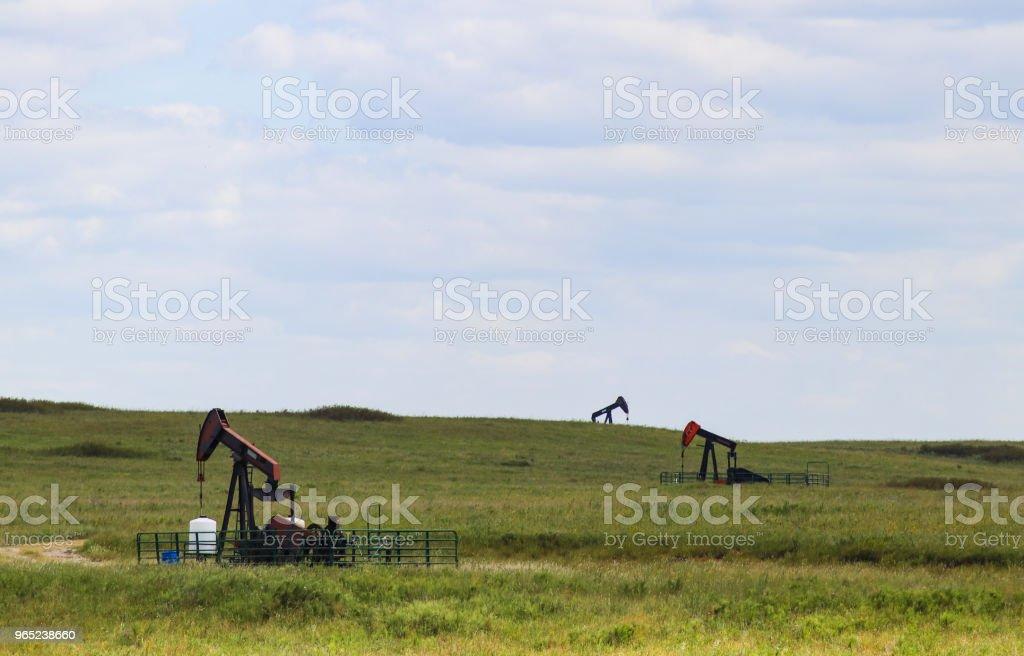 Three working pump jacks on oil or gas wells out in a green field zbiór zdjęć royalty-free