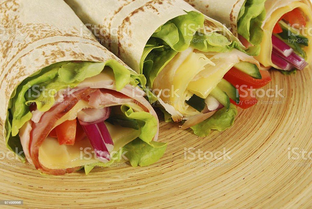 Three wrap sandwiches on wooden tray royalty-free stock photo