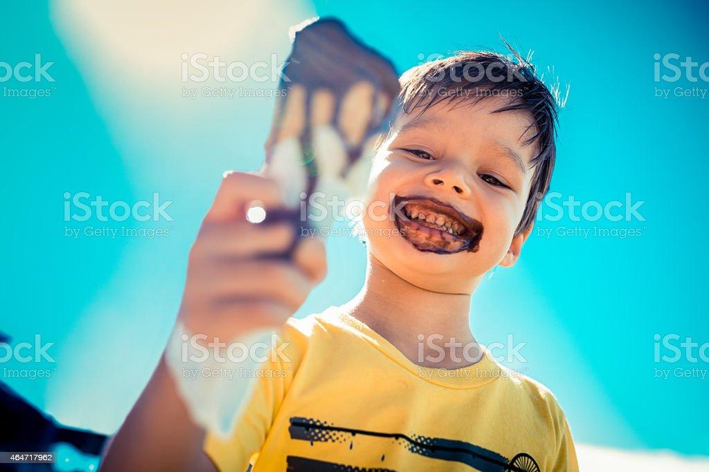 Three year old boy eats chocolate icecream stock photo