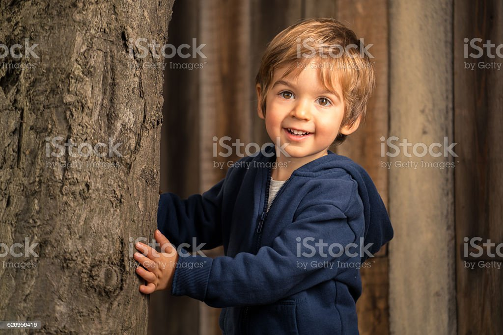 three year old kid that is peering behind a tree stock photo