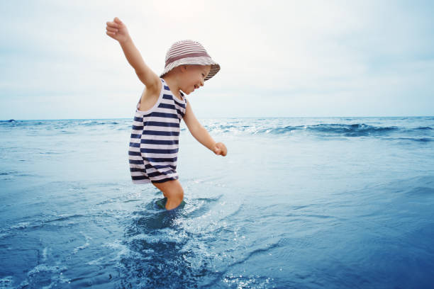 three years old boy playing at the beach in the water stock photo
