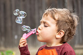 Caucasian three years old child boy blowing bubbles at his backyard