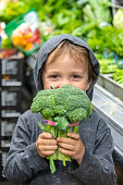 Caucasian Three years old child boy holding broccoli looking at the camera at the supermarket greengrocer section aisle