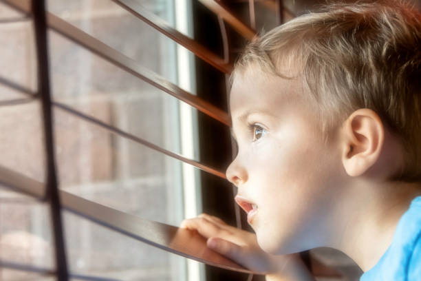 three years old child boy looking through a window three years old caucasian child boy looking through a window boy looking out window stock pictures, royalty-free photos & images