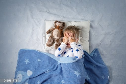 istock Three years old child crying in bed 1043561778