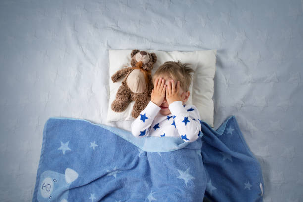 Three years old child crying in bed stock photo