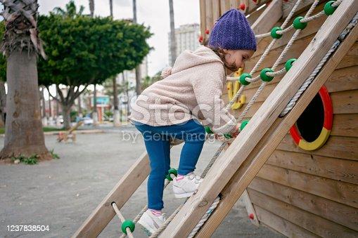 istock Three years old child having fun in a playground 1237838504