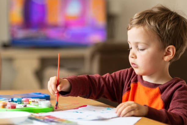 Three years old child painting with watercolors Three years old child painting with watercolors at the playroom eastern european descent stock pictures, royalty-free photos & images