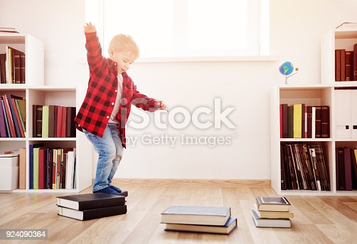 istock Three years old child sitting among books at home 924090364