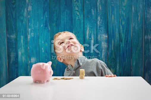 istock three years old child sitting st the table with money and a piggybank 914846994
