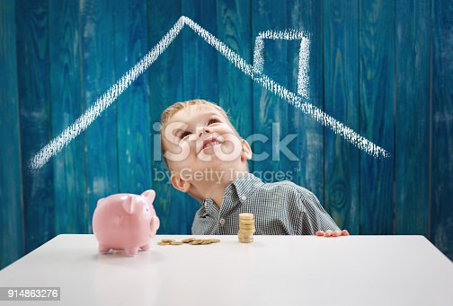 istock three years old child sitting st the table with money and a piggybank 914863276