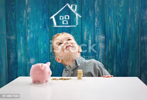 istock three years old child sitting st the table with money and a piggybank 914867530