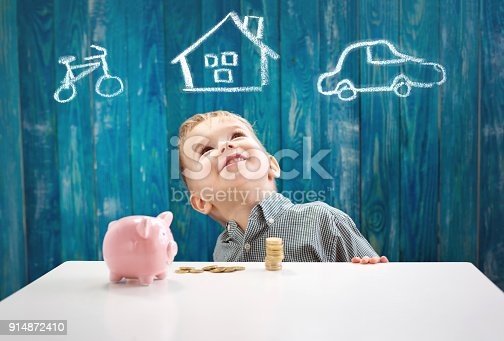 istock three years old child sitting st the table with money and a piggybank 914872410